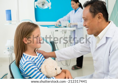 Experienced dentist supporting his young patient, side view - stock photo