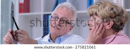 Experienced doctor analyzing with patient x-ray photo - stock photo