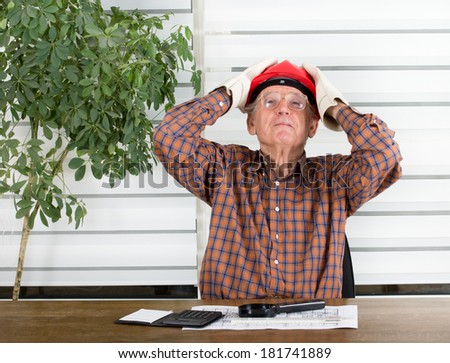 Experienced engineer with helmet holding his head and looking up - stock photo