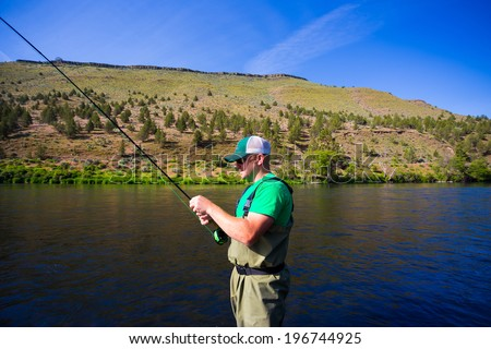 Experienced fly fisherman fishing the Deschutes River in Oregon, casting for fish while standing in the water. - stock photo
