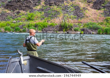 Experienced fly fisherman fishing the Deschutes River in Oregon, casting for fish while standing in the water.