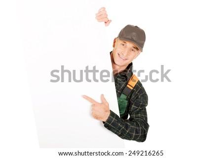 Experienced gardener in uniform showing empty banner - stock photo