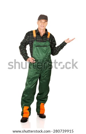 Experienced gardener in uniform showing space on the left - stock photo