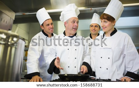 Experienced head chef explaining food to his colleagues in the kitchen - stock photo