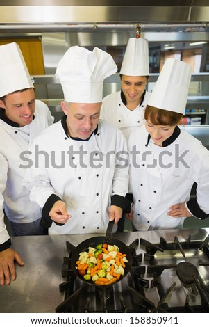 Experienced head chef explaining something to his colleagues in the kitchen - stock photo