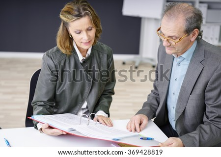 experienced manager in a meeting discussing papers - stock photo