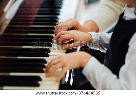experienced master piano hand helps the student, close-up - stock photo