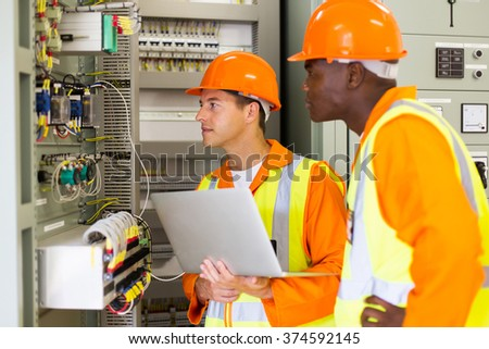 experienced multiracial industrial technicians checking transformer - stock photo