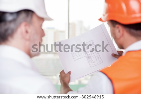 Experienced old architect and young foreman are working on plan of building. The worker is holding a blueprint. The men are looking at sketches with concentration. Focus on a paper - stock photo