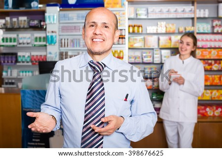 Experienced pharmacist counseling female customer in medical farmacy