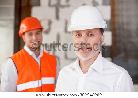 Experienced senior architect and a foreman are in process of building. They are standing and looking at the camera with joy. The men are smiling - stock photo