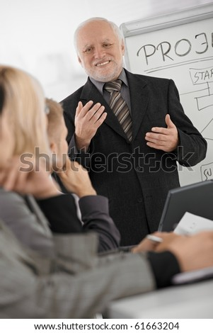 Experienced senior executive explaining work to colleagues, gesturing, smiling, standing at whiteboard.? - stock photo