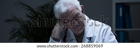 Experienced senior medic suffering for depression - panorama - stock photo