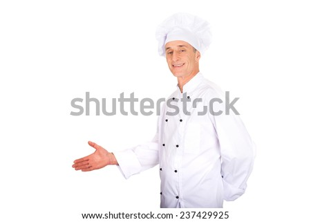 Experienced smiling chef showing copyspace on the left - stock photo