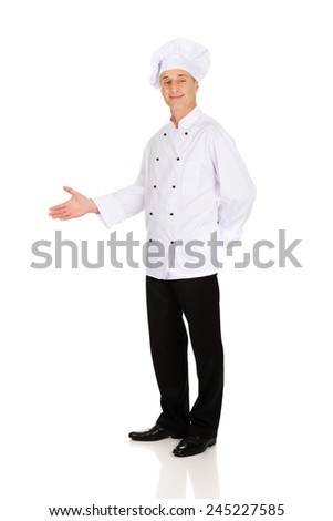 Experienced smiling chef with welcome gesture - stock photo