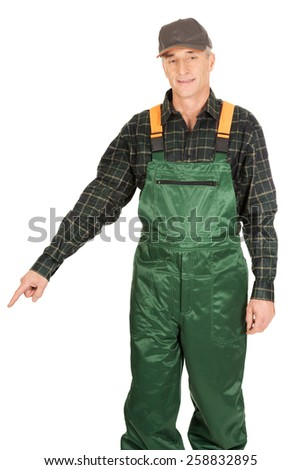 Experienced smiling gardener in uniform pointing down - stock photo