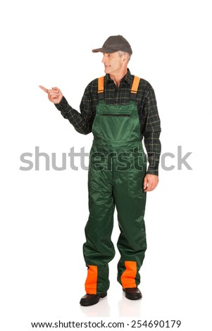 Experienced smiling gardener in uniform pointing to the left - stock photo