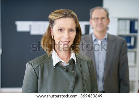 experienced successful businesswoman with her co-worker standing in background