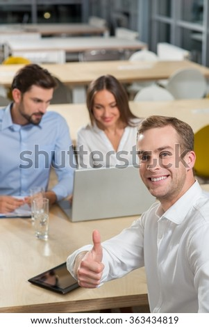 Experienced three business partners are working on new project. They are sitting at the table and smiling. The businessman is giving thumb up and looking at camera. Man and woman are using laptop - stock photo