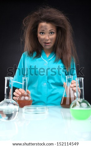 Experiment failed. Frustrated young woman in lab coat holding laboratory glasses and looking at camera while isolated on black