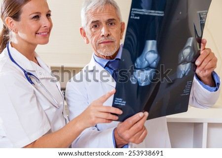 Expert doctor analyzing x-ray scan with female assistant. - stock photo