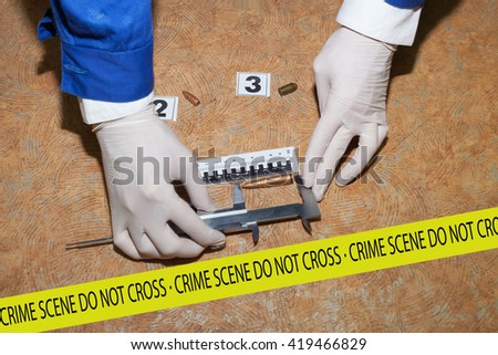 Expert examines a bullet at the crime scene.  - stock photo