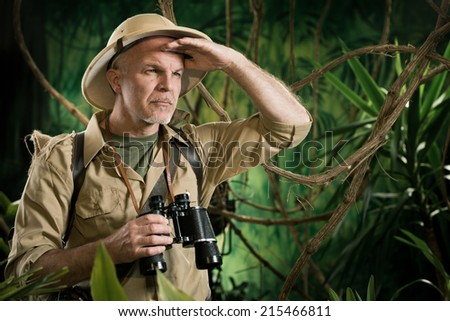 Expert explorer in the forest looking away and holding binoculars. - stock photo