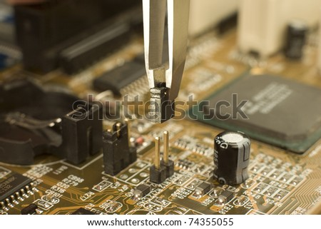 expert is putting electrical jumper on motherboard contacts with miniature forceps to lock electrical circuit - stock photo