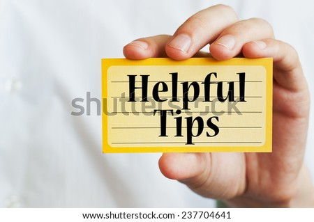 Expert showing a card with Helpful Tips written on it - Education concept - stock photo