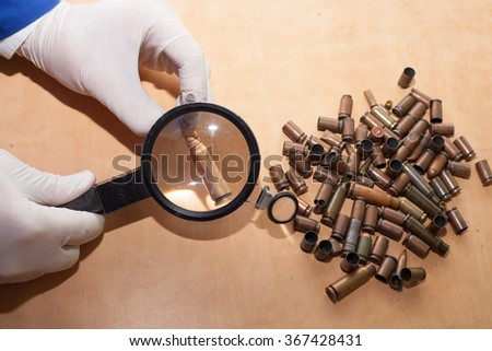 expert through a magnifying glass looking at a bullet - stock photo