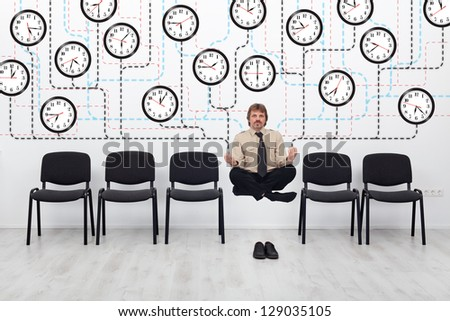 Expert time management - businessman controlling lots of wall clocks - stock photo
