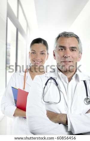 expertise gray hair doctor beautiful nurse in hospital white corridor [Photo Illustration] - stock photo