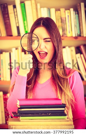 Exploration education concept. intelligent funny hipster student girl in library, woman holding magnifying glass loupe. Instagram filter - stock photo