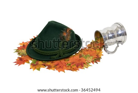 Explore fall traveling shown by stein pouring leaves to a green felt Alpine hat with rope twists and bright feathers - path included - stock photo