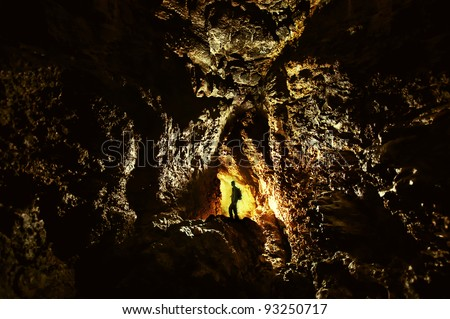 explorer in a cave with golden light in darkness - stock photo