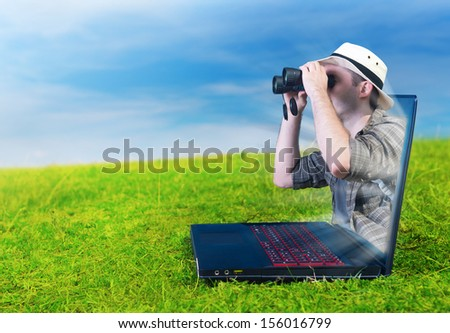 Explorer looking through binoculars from a laptop - stock photo