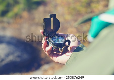 Explorer or traveler consulting a classical handheld compass as navigational instrument in order to find the right direction to the destination - stock photo