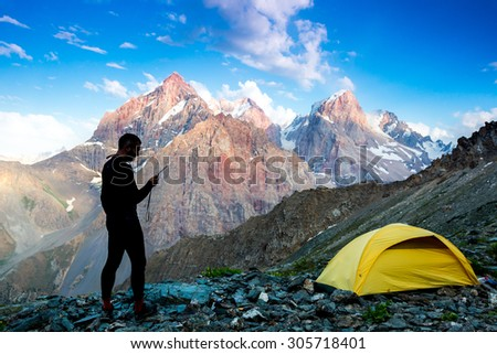 Explorer talking via radio station. Silhouette of man in wild mountain landscape walk along yellow camping tent holding radio transmitter connection with team blue sky sunny evening - stock photo