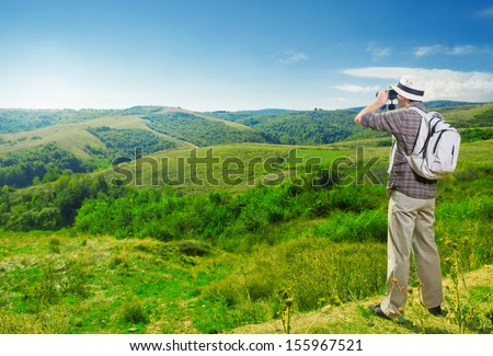 Explorer watching beautiful landscape through binoculars - stock photo