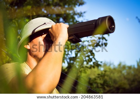 exploring scientist observing romantic male in pith helmet having fun looking in magnification scope on summer sunny day green woods & blue sky outdoors copy space background portrait picture - stock photo