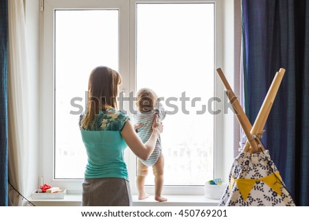 Exploring the world together. Side view of beautiful young woman holding her baby boy while standing at windowsill at home - stock photo