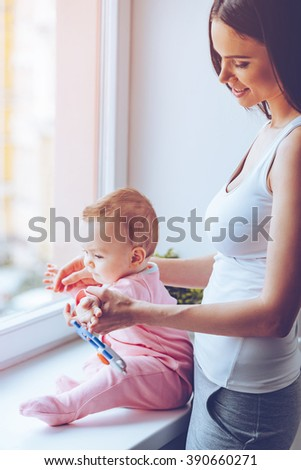 Exploring the world together! Side view of beautiful young woman holding her baby girl while standing at windowsill at home - stock photo