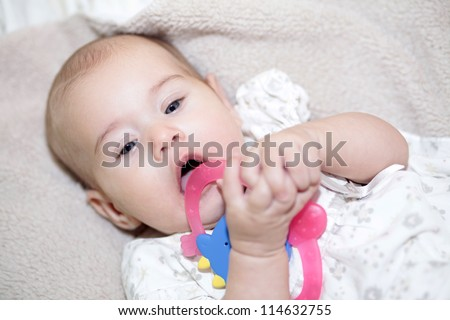 Exploring world. Little baby holding toy in mouth - stock photo