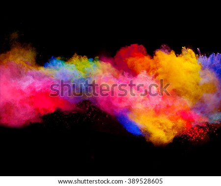 Explosion of colored powder on black background - stock photo
