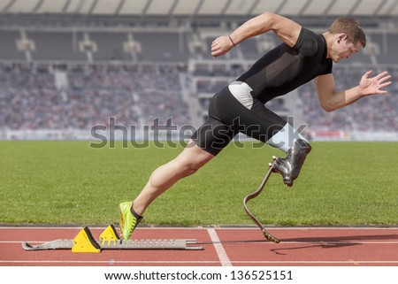 Explosive start of athlete with handicap - stock photo