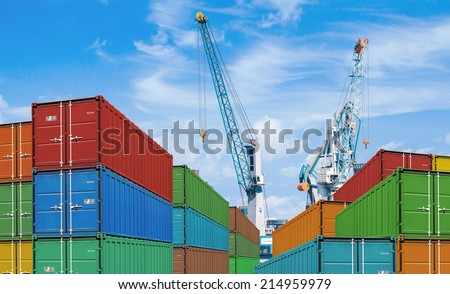 export or import shipping cargo container stacks and port cranes - stock photo