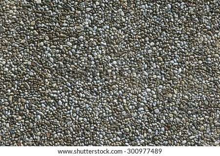 Exposed aggregate concrete with gray pebbles in closeup, taken at an older facade of the 80s  - stock photo