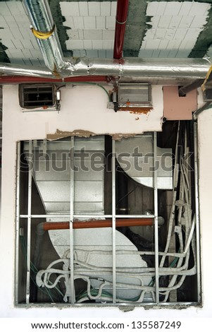 Exposed in-wall installation of HVAC air-conditioning system air ducts, located in an office building still undergoing construction. - stock photo