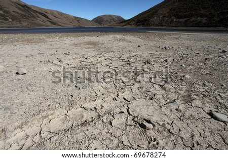 Exposed lake bed in the high country of New Zealand after a dry summer period - stock photo