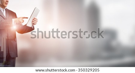 Exposure of city and businessman using tablet device as development concept - stock photo